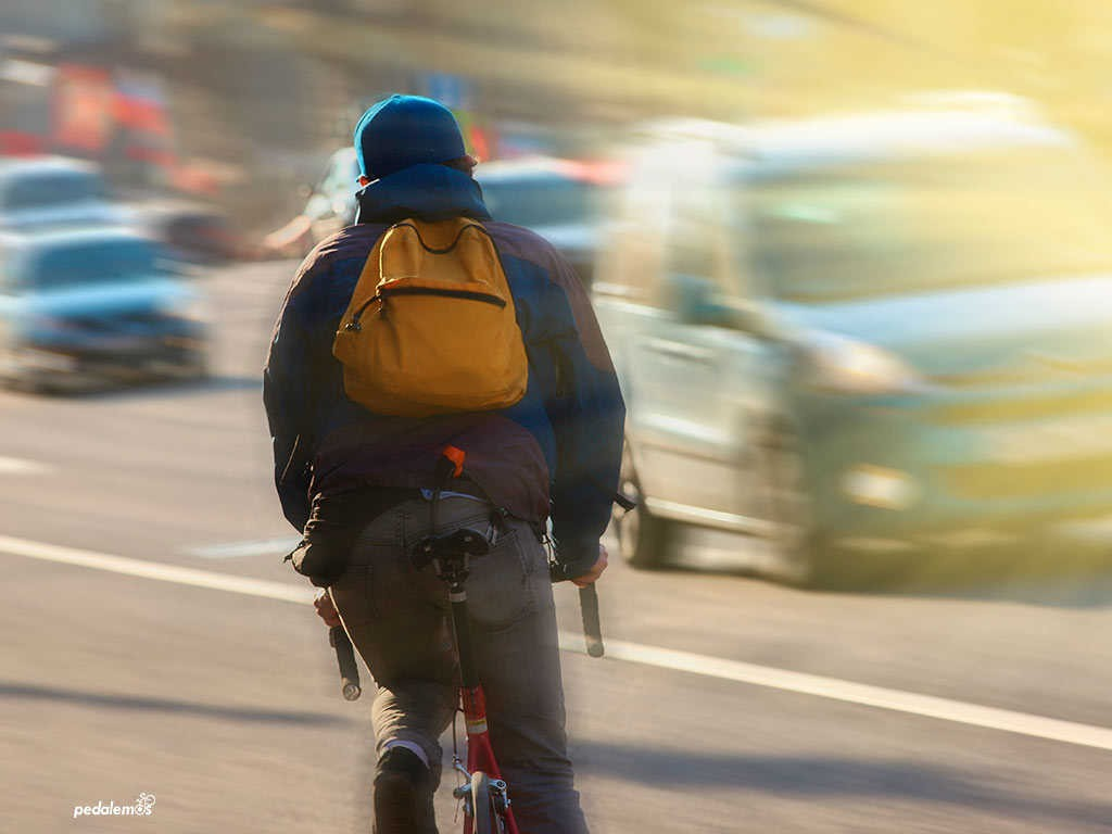 Rapaz pedalando pelas ruas - RHG Corretora de Seguros