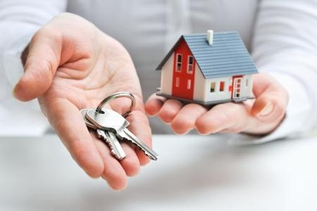 Home segurando chaves e casa miniatura - RHG Seguros