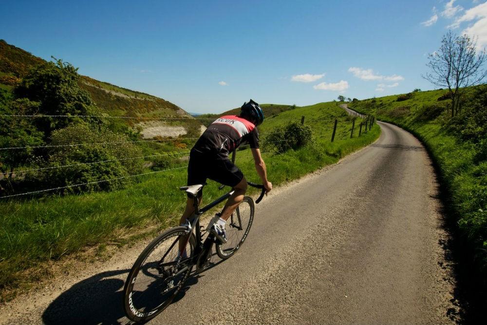 Ciclista subindo uma serra - RHG Seguros